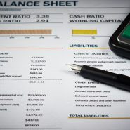 A pen and calculator laying on top of a balance sheet