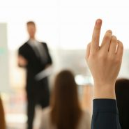A hand raised in a professional meeting setting