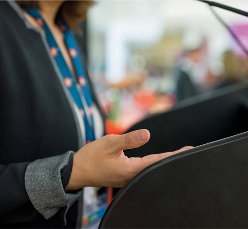 A female's hand on a podium while she is giving a presentation
